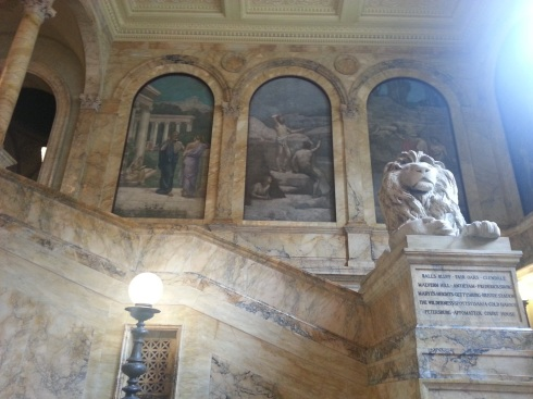 Beautiful paintings adorn marble walls within the library.